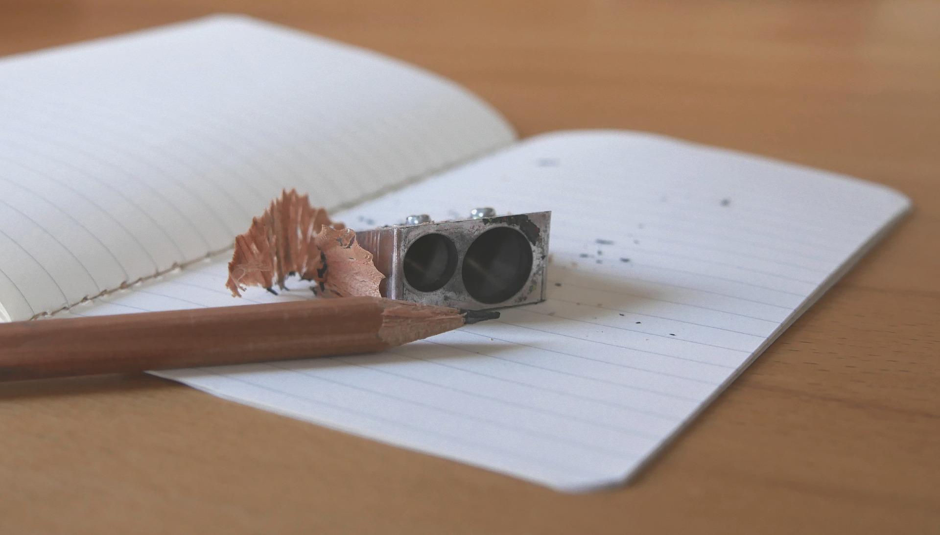 Cuaderno abierto con lapicero y sacapuntas